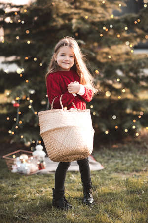 Happy child girl 3-4 year old wearing knitted red sweater holding straw bag decorate Christmas tree with xmas decor outdoors close up. Looking at camera. Childhood. New Year. Archivio Fotografico