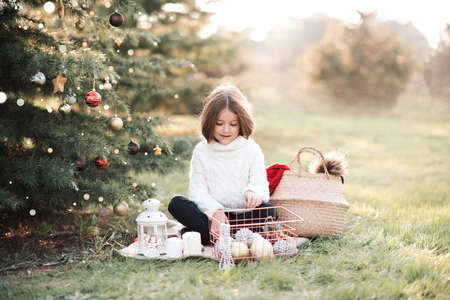 Smiling baby girl 3-4 year old decorate Christmas tree outdoors close up. Happiness. Winter holiday season. Childhood.