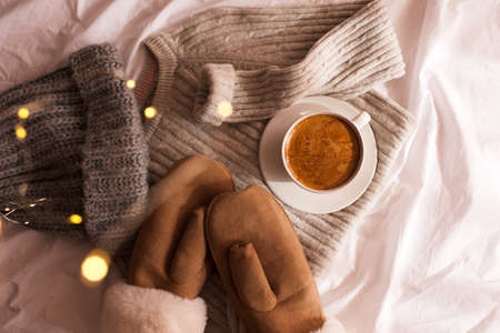 Winter clothes: knitted hat, mittens, woolen sweater and cup of coffee in bed closeup. Top view. Good morning. Winter holiday season.
