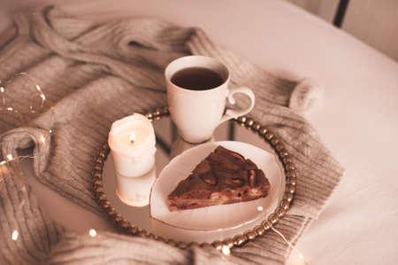 Chocolate pie with cup of tea and burning candle on tray with knitted sweater in bed close up. Good morning. Winter season.