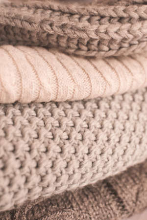 Set of cozy knitted sweaters in stack close up. Winter season.
