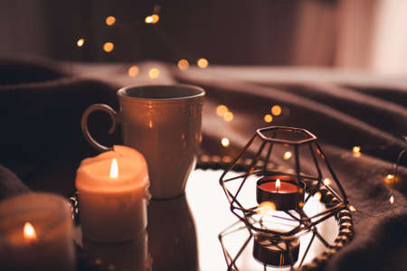 Cup of hot tea with burning candles on tray in bed over Christmas lights close up. Night time atmosphere at home. Archivio Fotografico