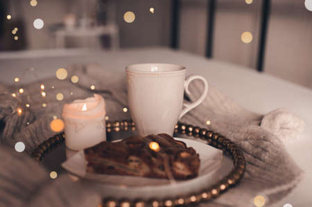 Cup of coffee with burning candle and chocolate pie in bed over Christmas lights close up. Good morning. Winter season.