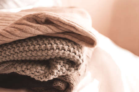 Stack of knitted cozy fabric at home close up. Winter season.