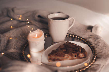 Mug of black tea with burning candle and chocolate pie in bed over Christmas lights close up. Good morning. Winter holiday season. Snack time. Archivio Fotografico