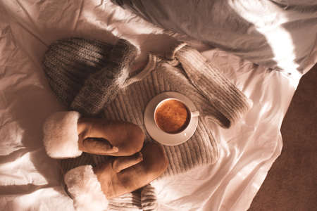 Cup of coffee with winter clothes: mittens, woolen sweater and hat in bed close up. Top view. Good morning.