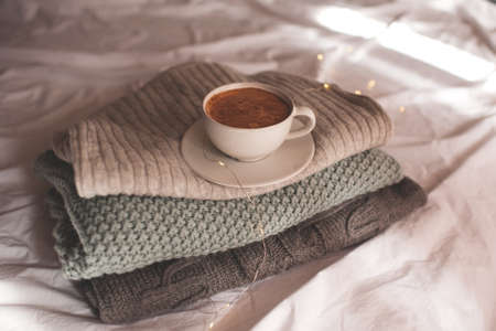 Cup of coffee with foam staying on stack of knitted sweaters close up. Good morning. Breakfast time. Winter season.