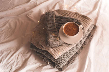 Winter holiday season concept: cup of fresh coffee on knitted sweaters close up. Good morning. Archivio Fotografico