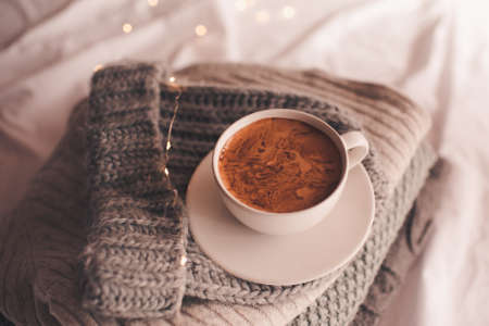 Mug of coffee on knitted fabrics in bed close up. Winter holiday season. Good morning.