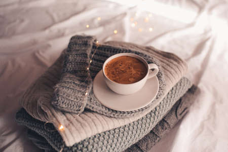 Cup of coffee staying on knitwear close up. Winter holiday season. Good morning.