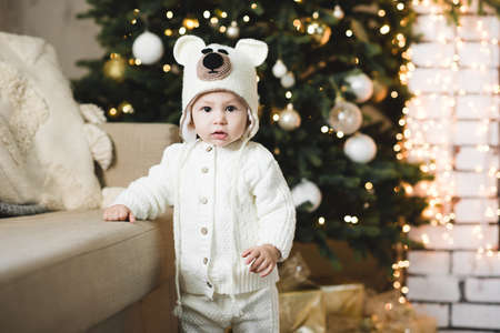 Cute baby girl 1 year old wearing knitted suit and hat posing over Christmas tree with glowing lights close up. Winter holiday season. Childhood. Looking at camera. New Year.
