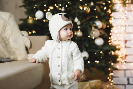 Cute baby girl 1 year old wearing knitted suit and hat posing over Christmas tree with glowing lights close up. Winter holiday season. Childhood. Archivio Fotografico