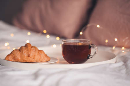 Cup of coffee with fresh croissant over Christmas lights close up. Good morning. Breakfast.
