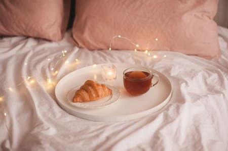 Cup of black tea with fresh tasty croissant staying on white tray over Christmas lights in bed close up. Good morning. Breakfast time.
