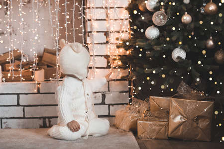 Baby 1-2 year old wearing knitted suit and hat sitting under Christmas tree with glowing lights and decorations close up. Winter holiday season. Childhood. Archivio Fotografico