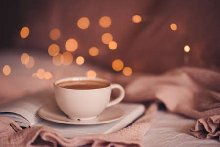 Tasty fresh cup of coffee on open paper book over Christmas lights close up. Good morning. Breakfast time. Winter holiday season. Archivio Fotografico