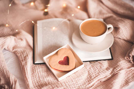 Cup of coffee staying on open book with heart shape cookie over lights close up. Good morning. Breakfast time. Valentines Day. Archivio Fotografico