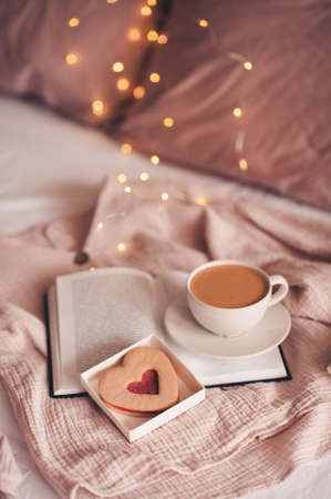 Cup of coffee with tasty heart shape cookie staying on open paper book. Good morning. Breakfast time. Valentines Day.