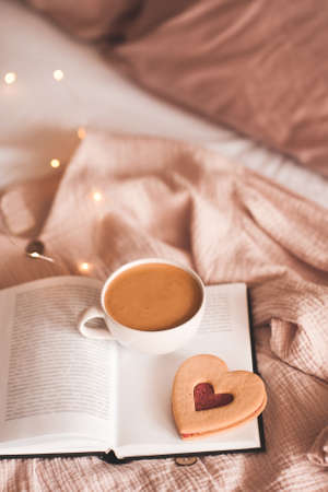 Cup of tasty coffee with red heart shape cookie on open paper book in bed over Christmas lights close up. Good morning. Breakfast. Valentines Day.