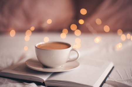 Cup of coffee stayin on open pepaer book over glowing Christmas lights close up. Good morning. Breakfast time. Xmas. Winter holiday time.