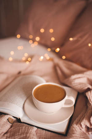 Cup of tasty hot coffee n open paper book over glosing Christmas lights in bed close up. Good morning. Breakfast time. Winter holiday season. Archivio Fotografico