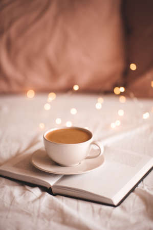 Mug of fresh tasty coffee on open paper book in bed over Christmas lights close up. Good morning. Winter holiday season. Breakfast time. Archivio Fotografico