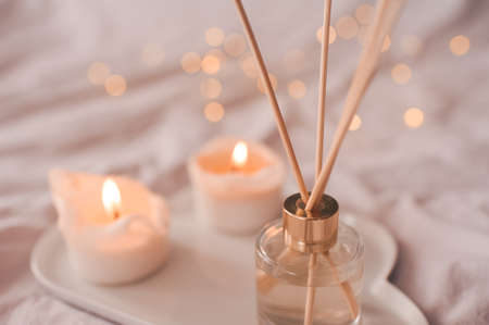 Home aroma fragrance diffuser with burning candles on white tray in bed over glowing lights close up. Cozy atmosphere. Wellness. Healthy lifestyle. Standard-Bild