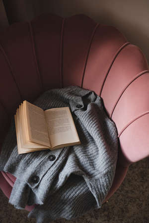 Open paper book with knitted wool fabric on cozy accent chair in room close up.