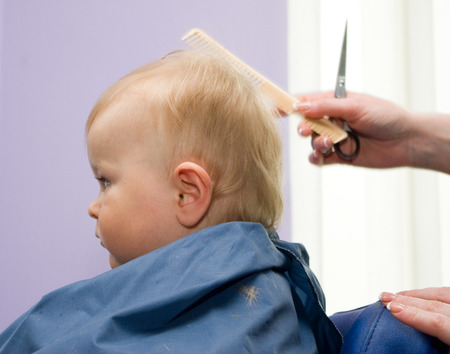 haircutting: Serious 1-year infant boy during his first haircutting