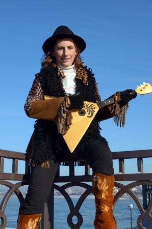 Lovely girl with balalaika is on embankment of Angara River in the city of Irkutsk Stock Photo - 17508799