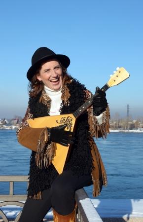 Lovely girl with balalaika is on embankment of Angara River in the city of Irkutsk Stock Photo - 17508796