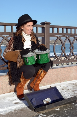 earns: The girl in the hat earns by playing drums on the city waterfront  Irkutsk
