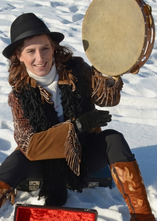 earns: Nice girl in a hat with a tambourine in the winter on the city waterfront  Irkutsk Stock Photo