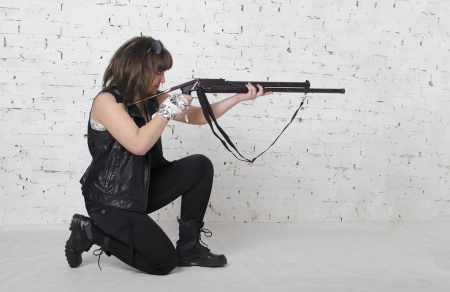 Young girl taking aim from a gun photo