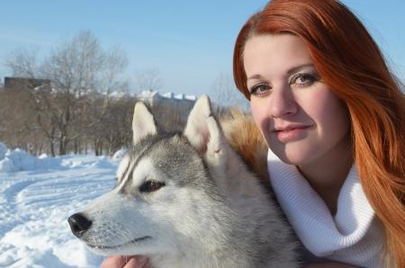 foxy girls: Portrate di giovane ragazza con un cane di razza husky in inverno sulla neve