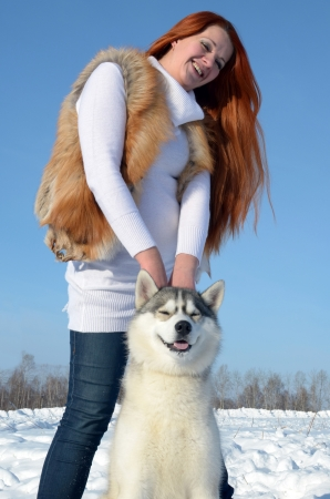 Young girl are standing with a dog of breed husky in the winter on the snow photo