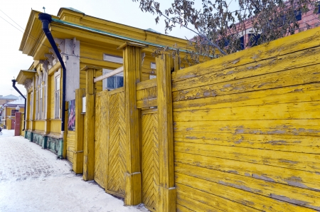 wicket door: Yellow flaked wooden fence with gate on winter street