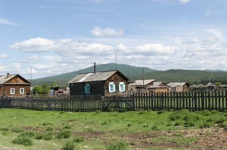Unpainted wooden house and a fence  Buryat village