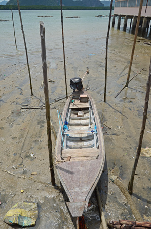 dais: Wooden boat at low tide in the floating village of sea gypsies in the Andaman Sea