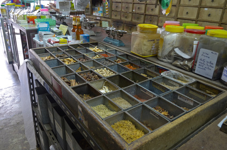 specialize: Containers with dried herbs in The Oldest Herbs Shop in the Old Town. Phuket, Thailand
