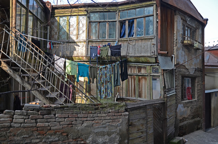 singularity: Old house with stairs and the laundry on the clothesline. Tbilisi, Georgia Editorial