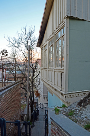 noteworthy: Wooden carved balcony and narrow street in the evening Stock Photo
