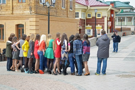 group shot: Irkutsk, Russia - May, 18 2015: A group of girls and photographer on the street in the city of Irkutsk. Back view