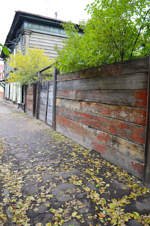 architectonics: Sidewalk with fallen yellow leaves and old shabby fence. Irkutsk street Stock Photo