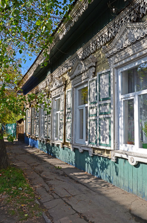 window shade: Lacy wooden house with window shutters in the shade of the leaves. Irkutsk streets, Russia