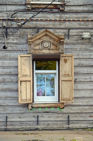 architectonics: Modern plastic windows framed by old wooden architraves and shutters. Irkutsk street, Russia Stock Photo