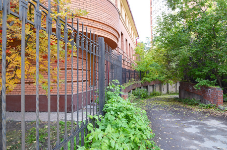 paling: Asphalt path, strewn with fallen leaves and the wall of a brick building behind the fence Stock Photo
