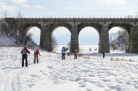 ski runs: Tourists-skiers go under Circum-Baikal Railway bridge. Irkutsk Region, Russia