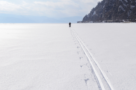 ski runs: Lone skier go through frozen lake Baikal. Siberia