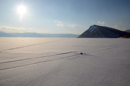 ski runs: Lone ski runs on surface of frozen lake Baikal at sunset. Siberia Stock Photo
